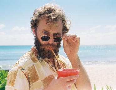 man drinking a cocktail on the beach